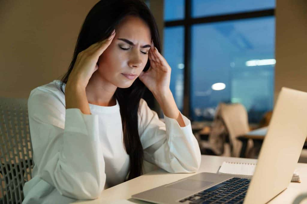 graphicstock-tired-fatigued-young-businesswoman-touching-her-temples-and-having-headache-in-office_r8KTivmdhx-scaled